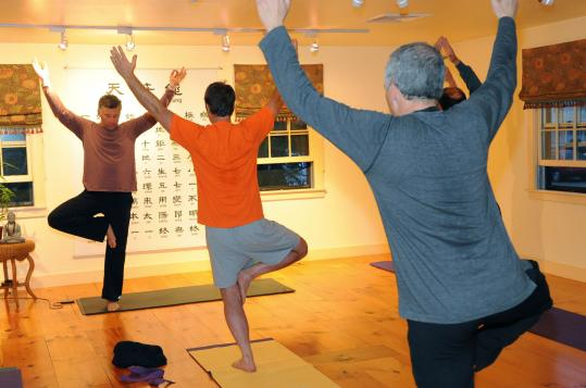 Mike Houlihan (left), owner of Roots to Wings yoga studio in Newbury's Byfield neighborhood, instructs Craig Grimes (center) and Jim Young, both of Byfield, during a class for men.