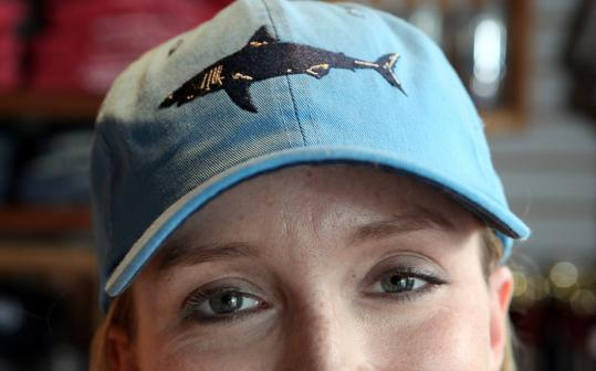 Manager Sara Liska modeled a hat at Chatham Clothing Bar, which has seen an increase in sales in shark-themed products.