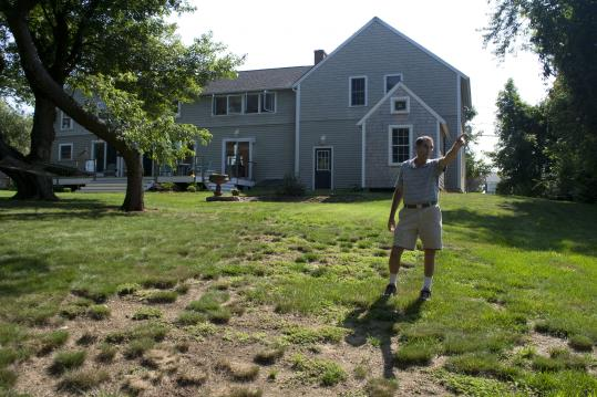 David Dardi points out his backyard view of Scituate&#8217;s new power-generating wind turbine.