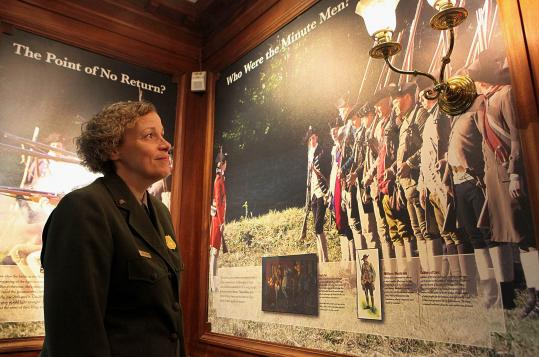 Park official Leslie Obleschuk takes in a new display at Concord's North Bridge Visitor Center that includes period artifacts (below left).