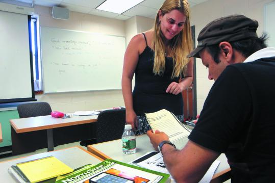 At an adult ESL class at Framingham State University, teacher Vanessa Desani assists a student, the Rev. Celso Lima.