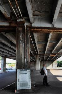 A commuter waited for a bus beneath the McCarthy overpass — a vestige of planning ideas from the 1950s, when the goal was to eliminate bottlenecks for auto drivers.