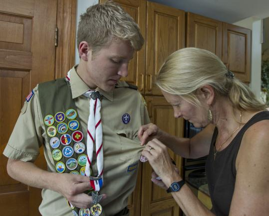 Ned Coltman and his mother, Judy, of Reading, removed his Eagle Scout badge from his Boy Scout uniform.