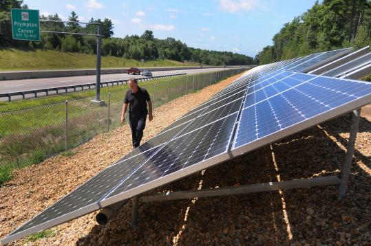 Jack Hunter, Carver's town planner, inspects the new solar panels set up along Route 44. Jack Hunter, Carver's town planner, inspects the Route 44 solar panels providing electricity for a water-treatment plant.
