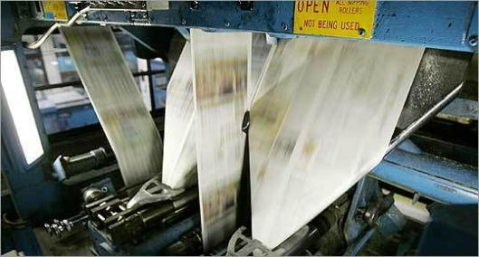 Papers run through machines at the Minneapolis Star Tribune production plant.