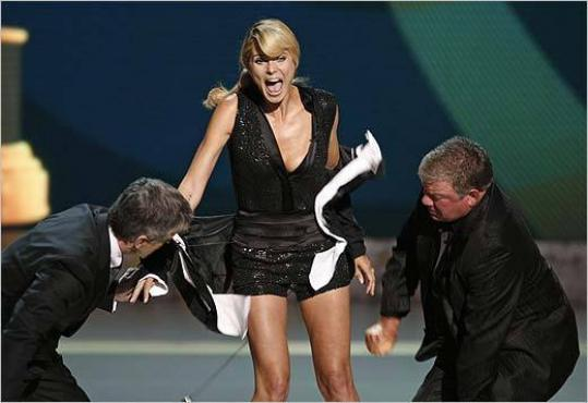 Host Tom Bergeron (left) and William Shatner strip host Heidi Klum of her tuxedo during the Emmy Awards last night.