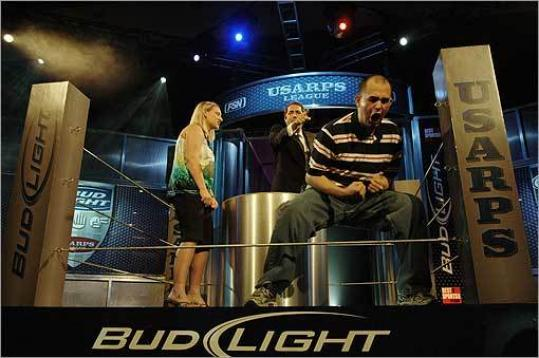 Runner-up Julie Crossley of Anderson, Indiana, left, watches as Sean Sears of Chicopee, Massachusetts, celebrates his victory in the 2008 Bud Light/USARPS League Championship at Mandalay Bay Hotel and Casino on June 22, 2008 in Las Vegas, Nevada.