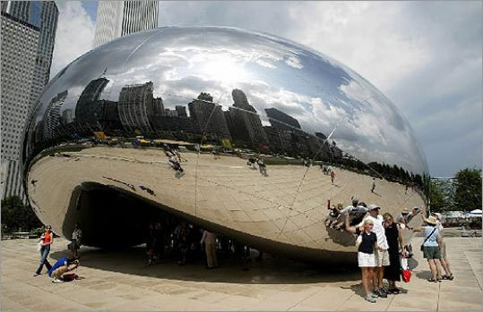 Chicago residents and tourists explore the Cloud Gate sculpture by Anish Kapoor at Chicago's Millennium park in 2004.