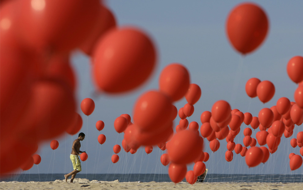 In this June 27, 2008 file photo, a man runs next to balloons placed at Copacabana beach, in Rio de Janeiro. Demonstrators released around 4,000 red balloons during an event representing the 4,000 people who were expected to become victims of violence over the next six months. (AP Photo/ Ricardo Moraes)