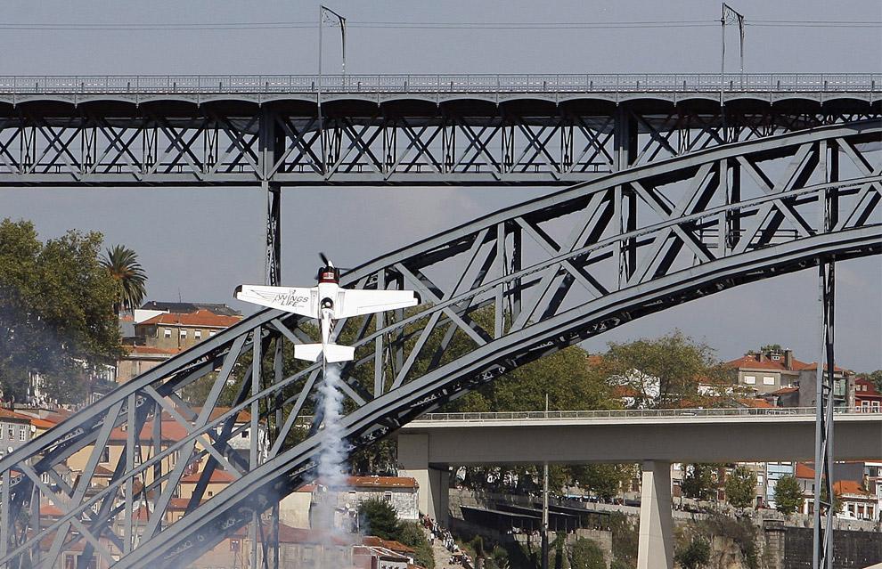 Майк Мангольд, из США, летит на своем самолете Edge 540 над рекой Дору в ходе седьмого этапа ежегодных соревнований Red Bull Air Race в Порто, 7 сентября 2008. На этих соревнованиях Мангольд занял третье место. (AP Photo/Paulo Duarte)
