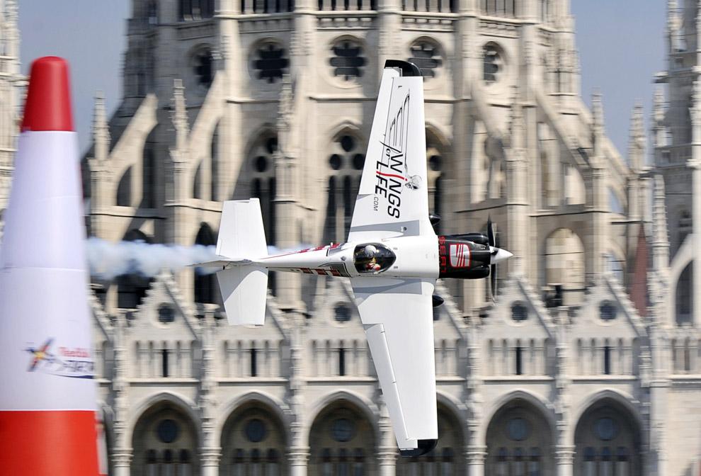 Американский пилот Майк Мангольд летит на своем Edge 540 над Дунаем в центре Будапешта во время шестого раунда чемпионата мира Red Bull Air Race 20 августа 2008. (ATTILA KISBENEDEK/AFP/Getty Images)