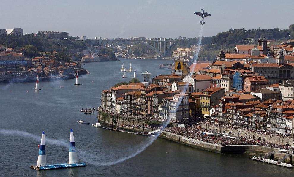 Глен Делл, пилот из Южной Африки, летит на своем Edge 540 над рекой Дору в ходе седьмого этапа ежегодных соревнований Red Bull Air Race в португальском городе Порто7 сентября 2008. (AP Photo/Paulo Duarte)