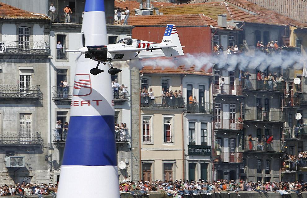 Майк Мангольд из Соединенных Штатах летит над рекой Дору в ходе седьмого этапа ежегодного соревнования Red Bull Air Race World в Порто, 7 сентября 2008. (AP Photo/Paulo Duarte)