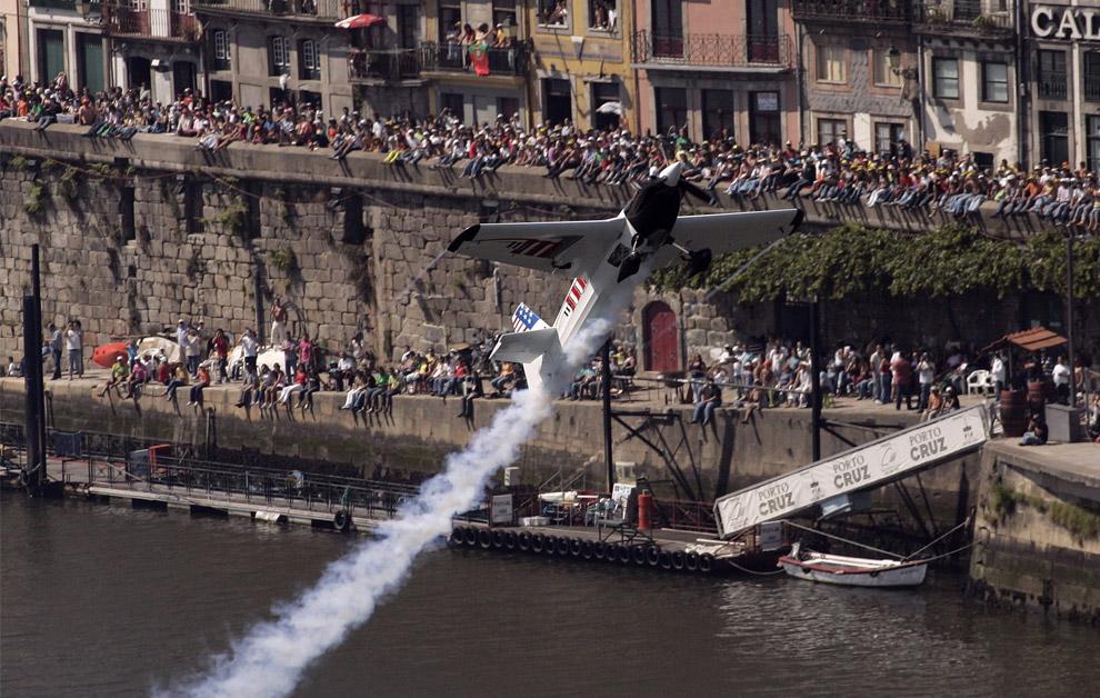 Американский пилот Майк Мангольд на своем Edge 540 пролетает над рекой Дору в ходе седьмого этапа ежегодных воздушных гонок Red Bull Air Race World в Порто, 7 сентября 2008. (AP Photo/Paulo Duarte)