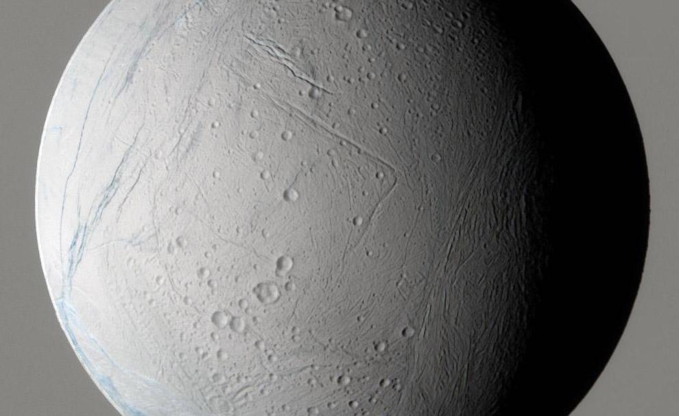 El Sol iluminando Encélado desde la izquierda, dejando parte de ella en la sombra