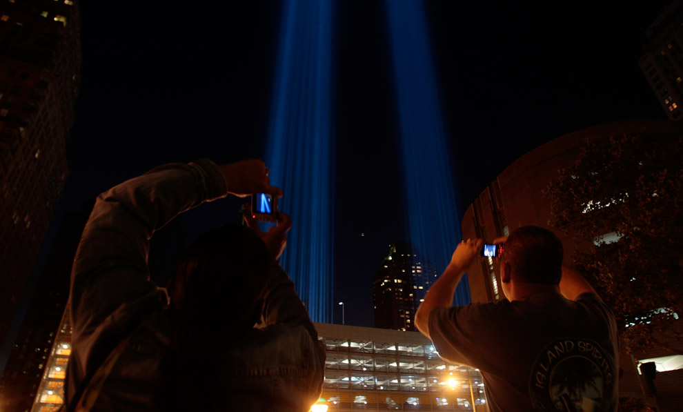 Зрители фотографируют мощные огни символизирующие Ground Zero (эпицентр взрыва(?) в Нижнем Манхэттене 11 сентября 2008 года в Нью-Йорке – во время седьмой годовщины террористических атак в США, в результате которых рухнул Всемирный торговый центр. (Photo by Chris Hondros/Getty Images)