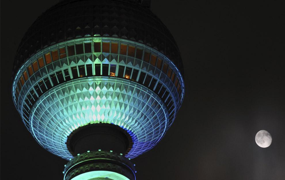 Луна в небе рядом с освещенной телевизионной башней Fernsehturm во время Фестиваля огней вечером в четверг, 16 октября 2008. (AP Photo/Sven Kaestner)