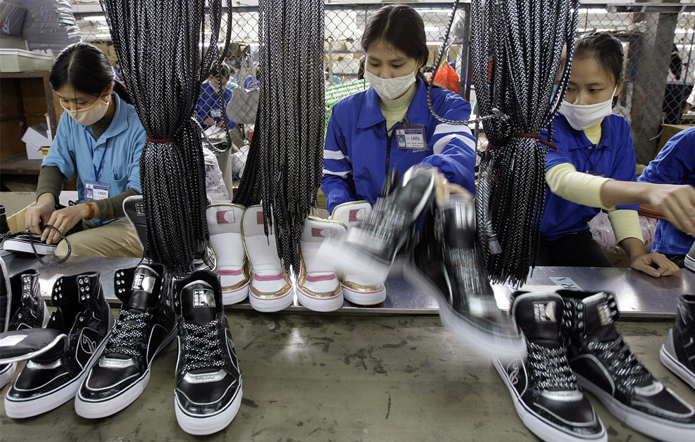 Khan Simom glues cushions to unfinished shoes during assembly at the New Balance Athletic Shoe factory