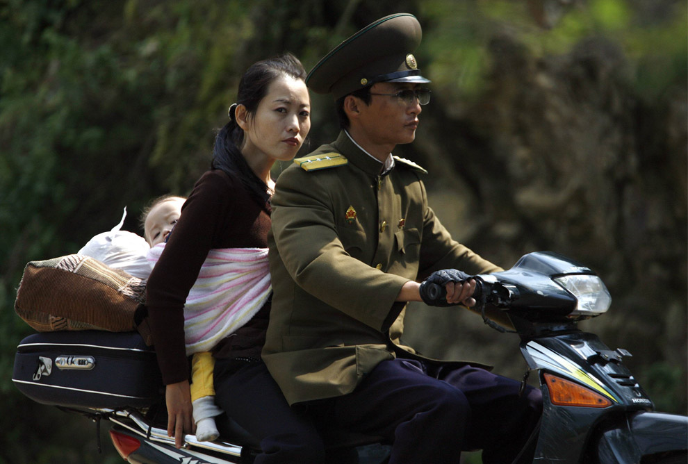 north korean women marching. A woman carrying a baby on her