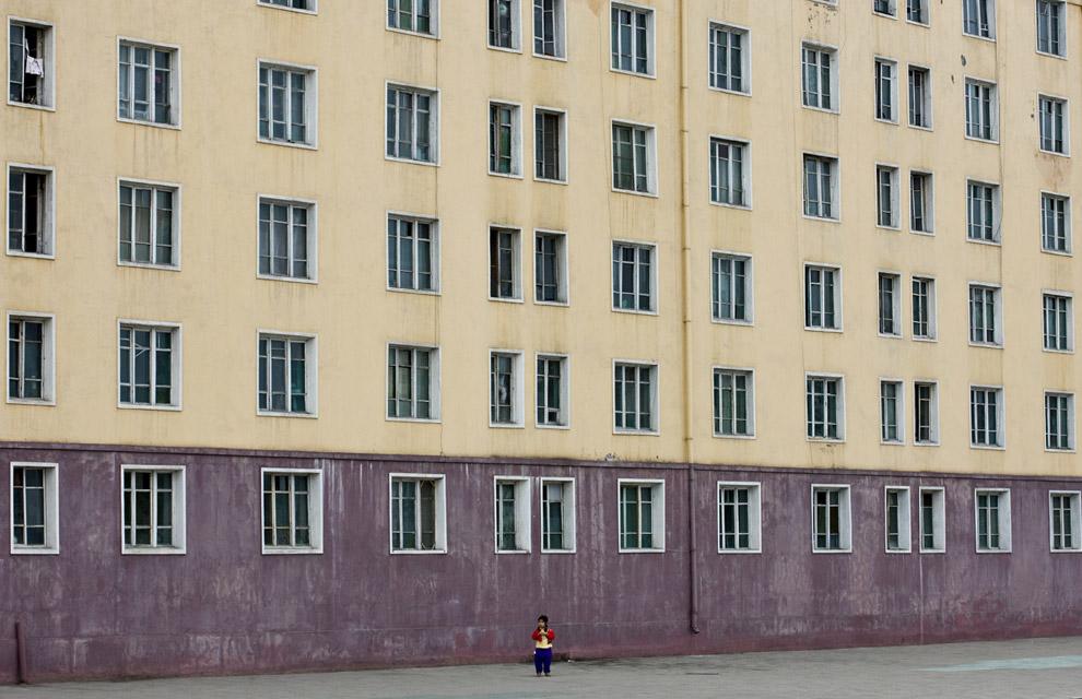 Ребенок на фоне жилого дома в Пхеньяне. 12 апреля 2008. Эрик Лафорг: В то все дети вместе со своими родителями участвовали в репетициях массовых игр. Поэтому все дома и улицы были абсолютно пустыми. Это выглядело очень непривычно…. (© Eric Lafforgue)