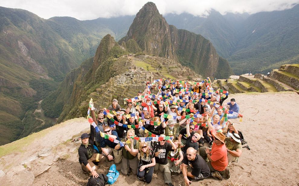 Добравшись наконец до Мачу-Пикчу, конечного пункта назначения, вся команда Peru Rocks позирует с флажками, на которых написаны пожелания. 13 октября 2008. (© Gary Noel)
