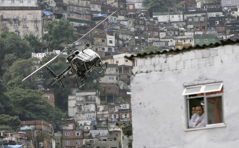 Полицейский вертолет пролетает над трущобами Rocinha во время полицейской операции в Рио-де-Жанейро, 2 июня 2008. Как сообщает посланником ООН Филип Олстон, бразильские полицейские совершают тысячи убийств, которые, в основном, остаются безнаказанными, поскольку полиция получает поддержку общественности в подавлении преступности. Согласно данным Бразильского Института общественной безопасности в столкновениях с полицией  в Рио-де-Жанейро в прошлом году погибло 1260 гражданских лиц. (AP Photo/Ricardo Moraes)