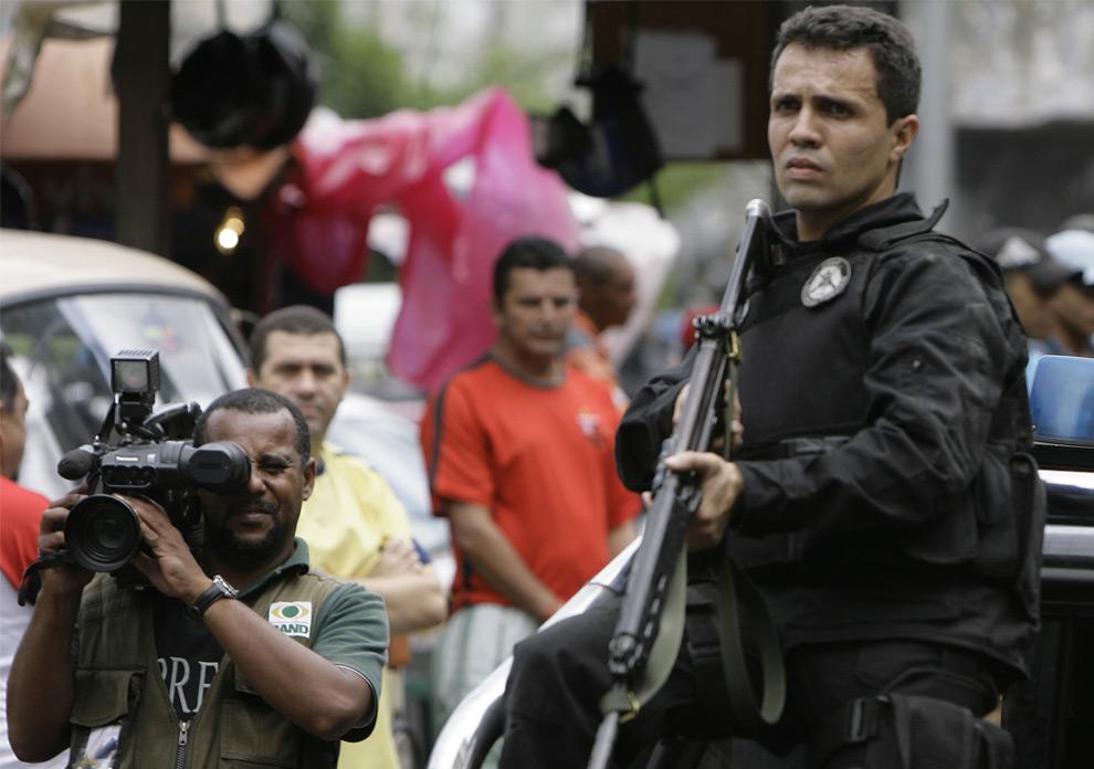 Оператор снимает полицейскую операцию на улицах трущоб Rocinha в Рио-де-Жанейро, 2 июня 2008. Два бразильских журналиста, проводивших расследование в трущобах Рио-де-Жанейро утверждают, что были похищены и подвергнуты пыткам со стороны вооруженных людей, которые назвались полицейскими, сообщает газета «O Dia». (AP Photo/Ricardo Moraes)