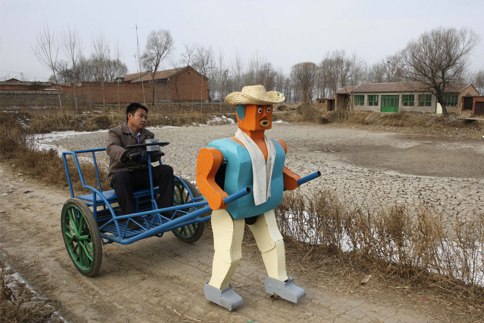 Farmer Wu Yulu drives his rickshaw pulled by a his self-made walking robot near his home in a village at the outskirts of Beijing January 8, 2009. This robot is the latest and largest development of hobby inventor Wu, who started to build robots in 1986, made of wire, metal, screws and nails found in rubbish sites. (REUTERS/Reinhard Krause) #