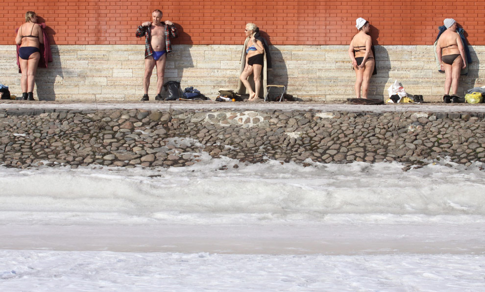 Elderly Russian men and women sunbathe near the wall of the Peter Paul fortress in St. Petersburg on March 16
