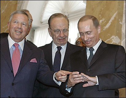 Robert Kraft (L) and Rupert Murdoch watched President Vladimir Putin try on the Patriots ring before he pocketed it.